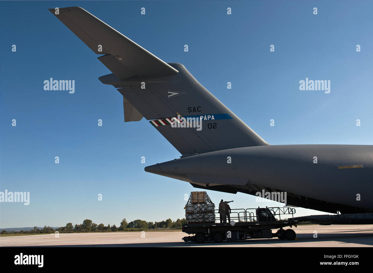 Aerial porters remove pallets from a C-17 Globemaster III after a recent Swedish mission. The HAW operates a fleet - Stock Image