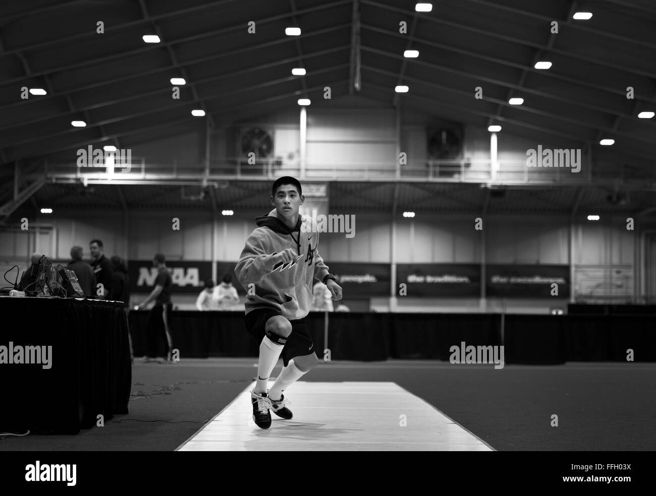 Prior to the start of the 2014 NCAA Fencing Championships, Alexander Chiang works on his form during a warmup period - Stock Image