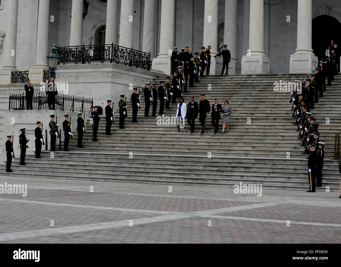 A joint honor guard salutes as role players representing the president, vice president and their spouses descend - Stock Image