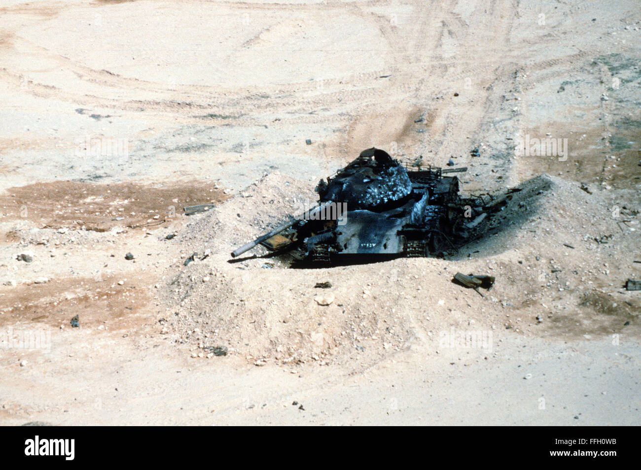 An Iraqi T-55 tank lies in ruins in the aftermath of an Allied bombing attack during Operation Desert Storm. - Stock Image