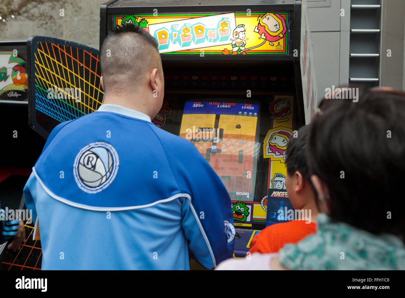 Young man playing Dig Dug arcade video game - USA - Stock Image