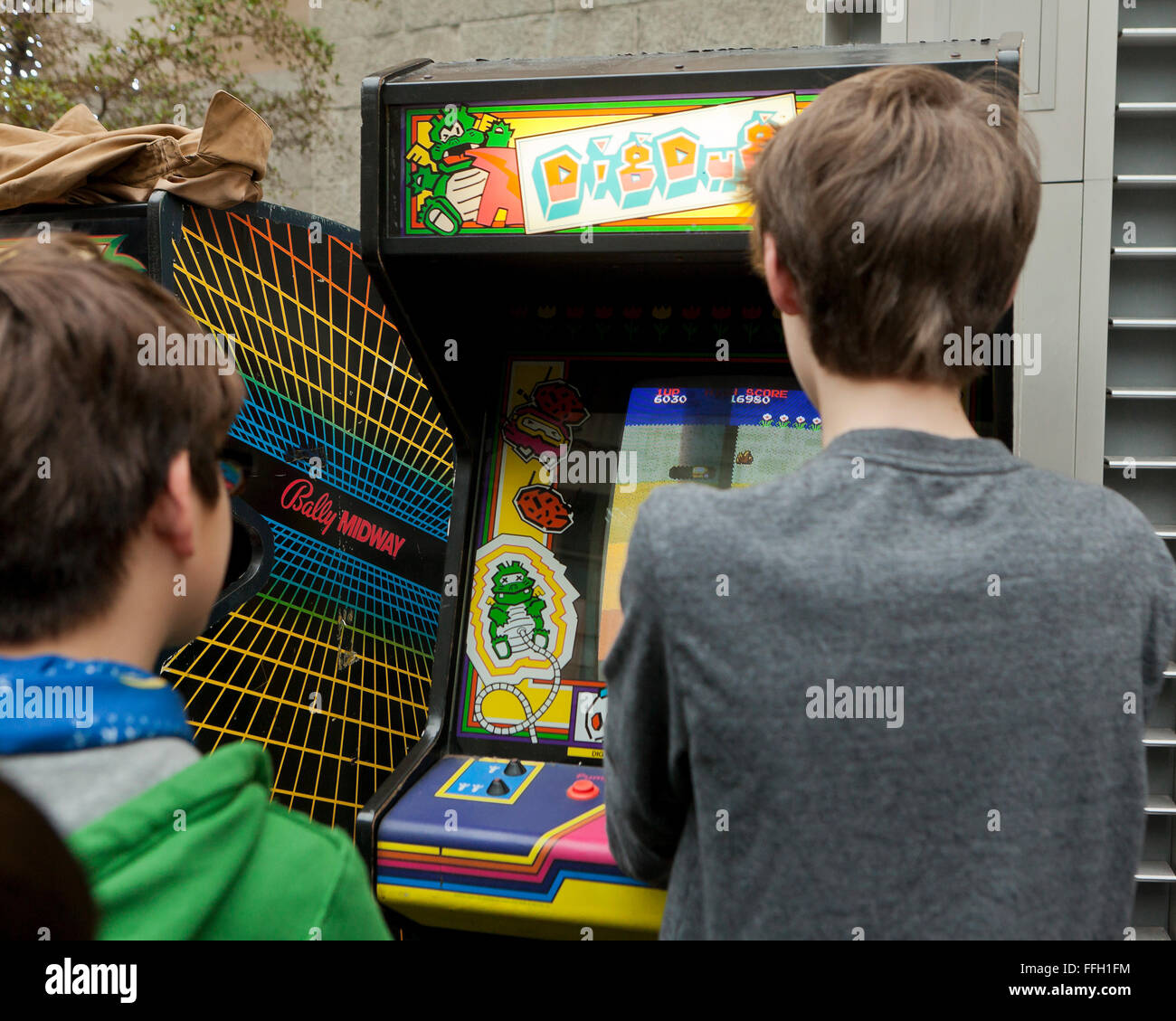 Young boys playing the classic Dig Dug video arcade game - USA - Stock Image
