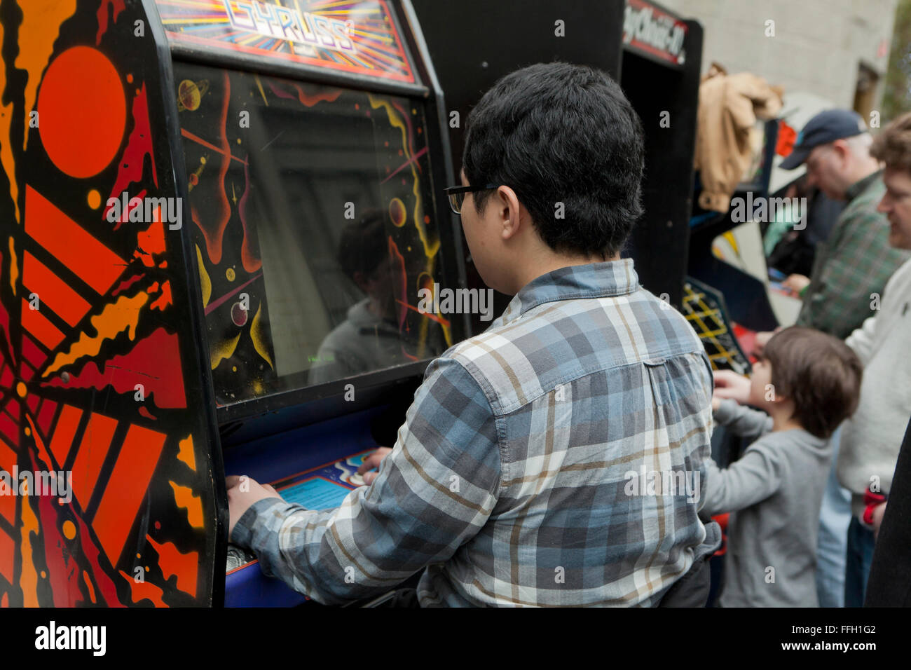 Young man playing arcade video game - USA - Stock Image