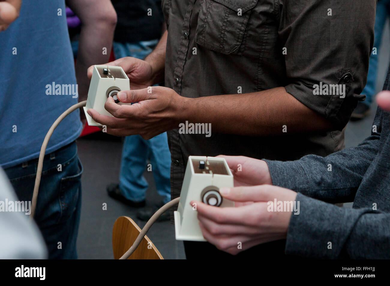 Men playing video game using vintage game controller - USA - Stock Image