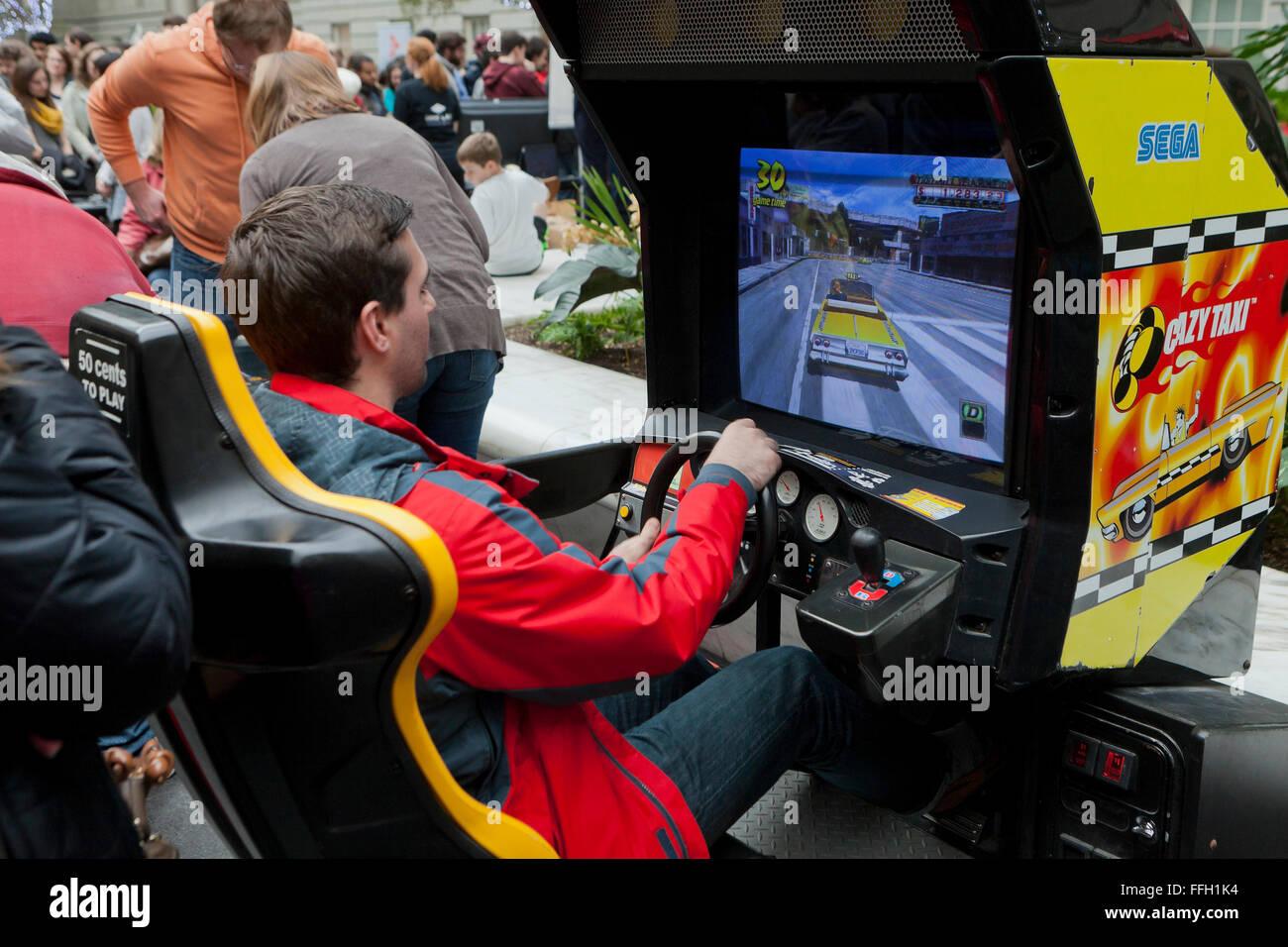 Man playing Sega Crazy Taxi arcade game - USA - Stock Image