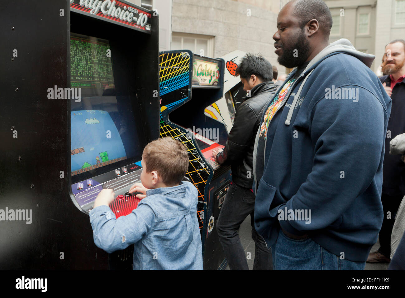Small child playing arcade video game - USA - Stock Image