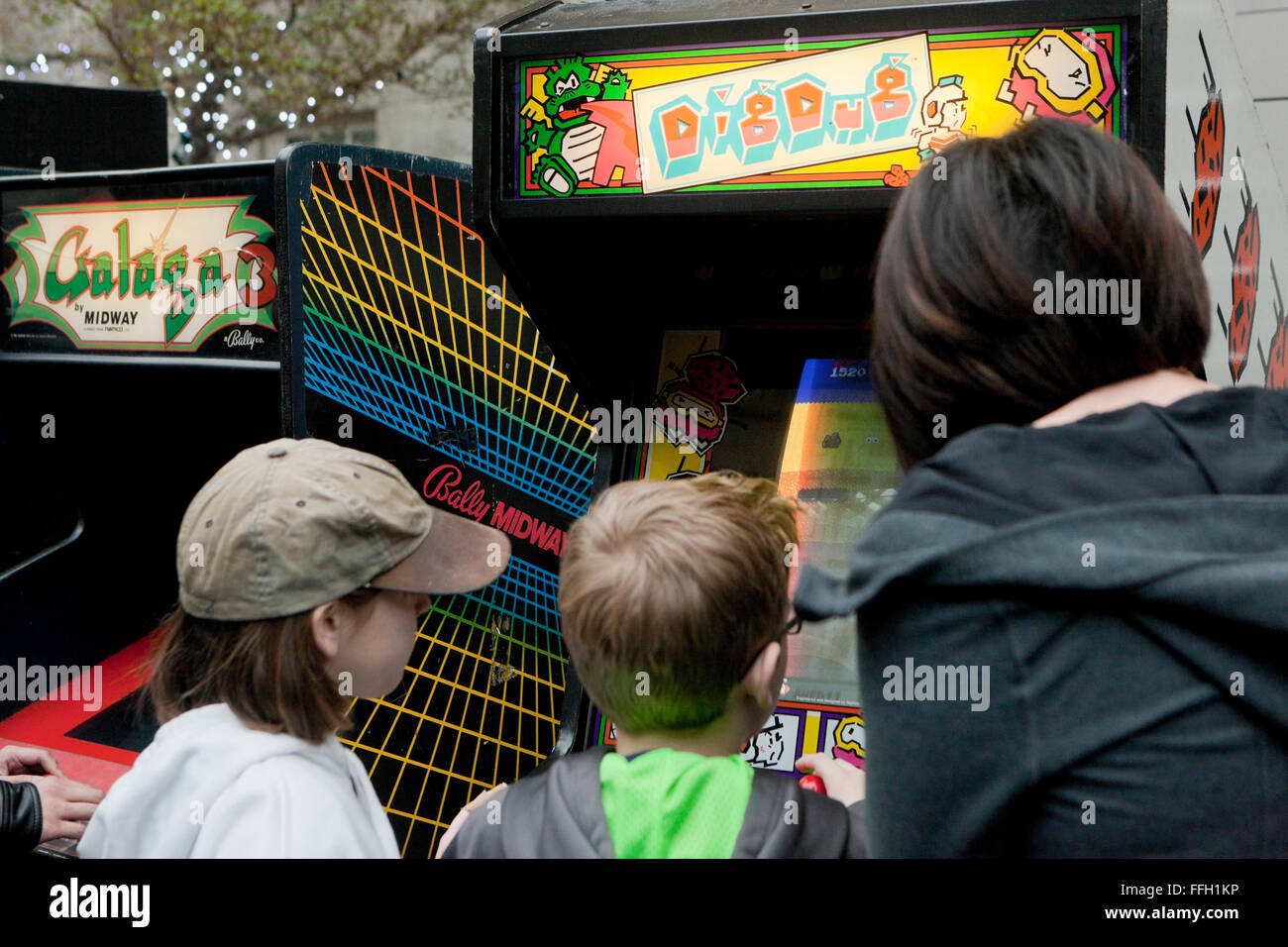 Children playing Dig Dug arcade video game - USA - Stock Image