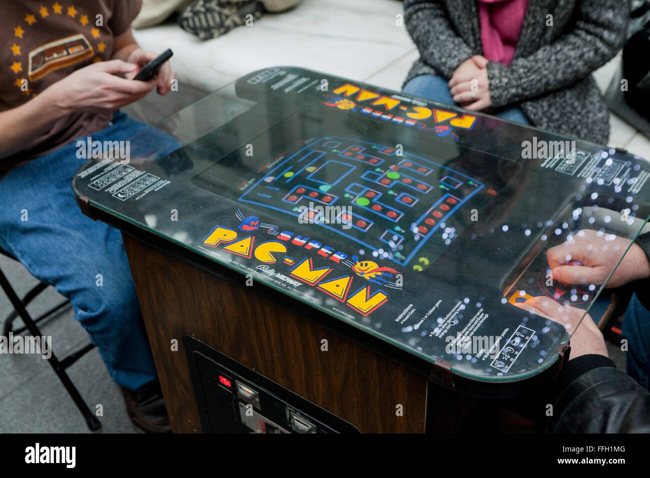 People playing a vintage Pac-Man video arcade game - USA - Stock Image