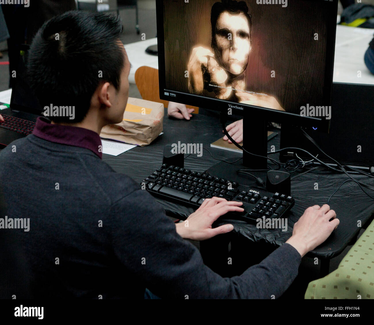 Asian man sitting in front of computer monitor - USA - Stock Image