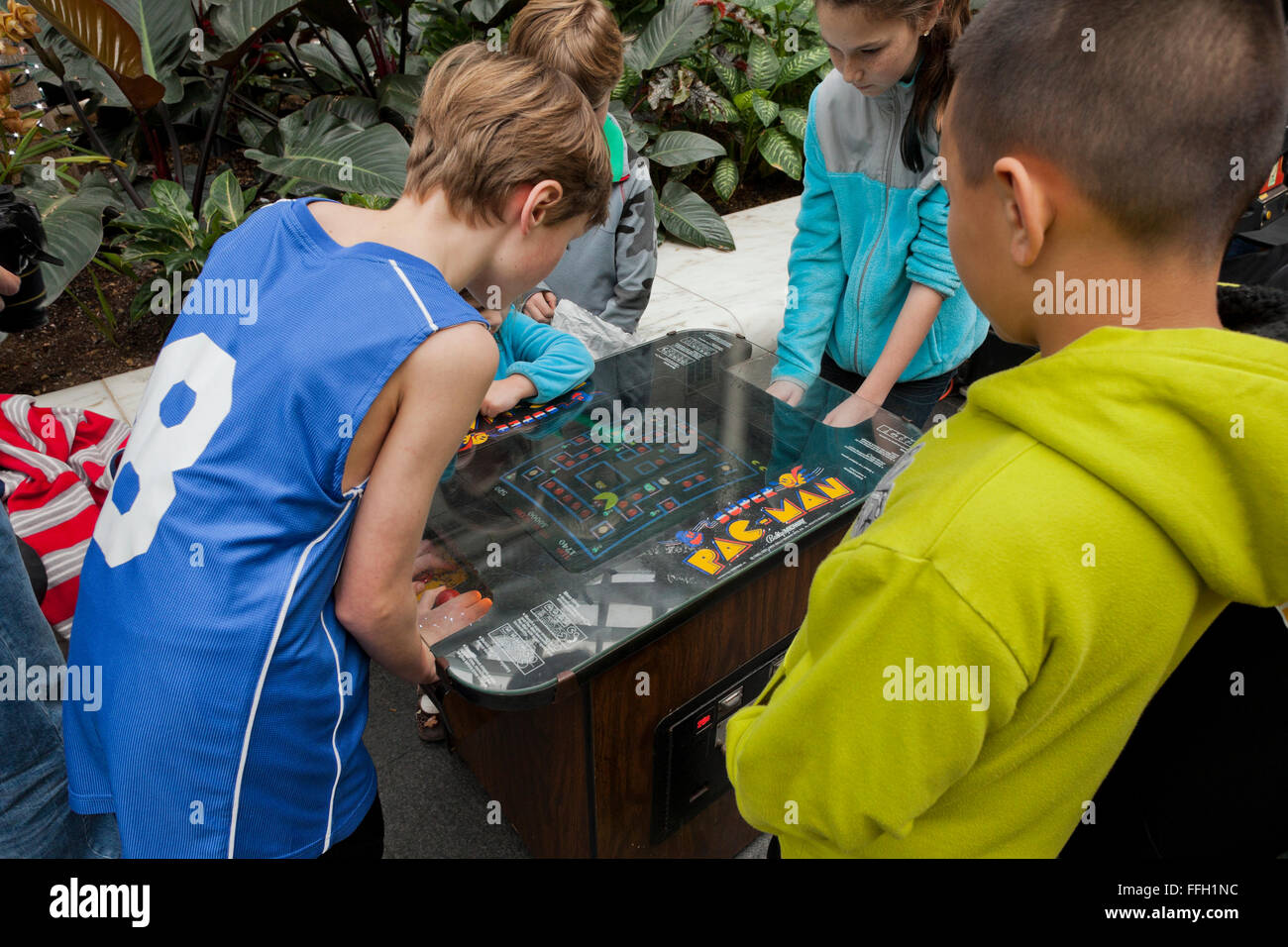 Young children playing the classic Pac-Man video arcade game - USA - Stock Image