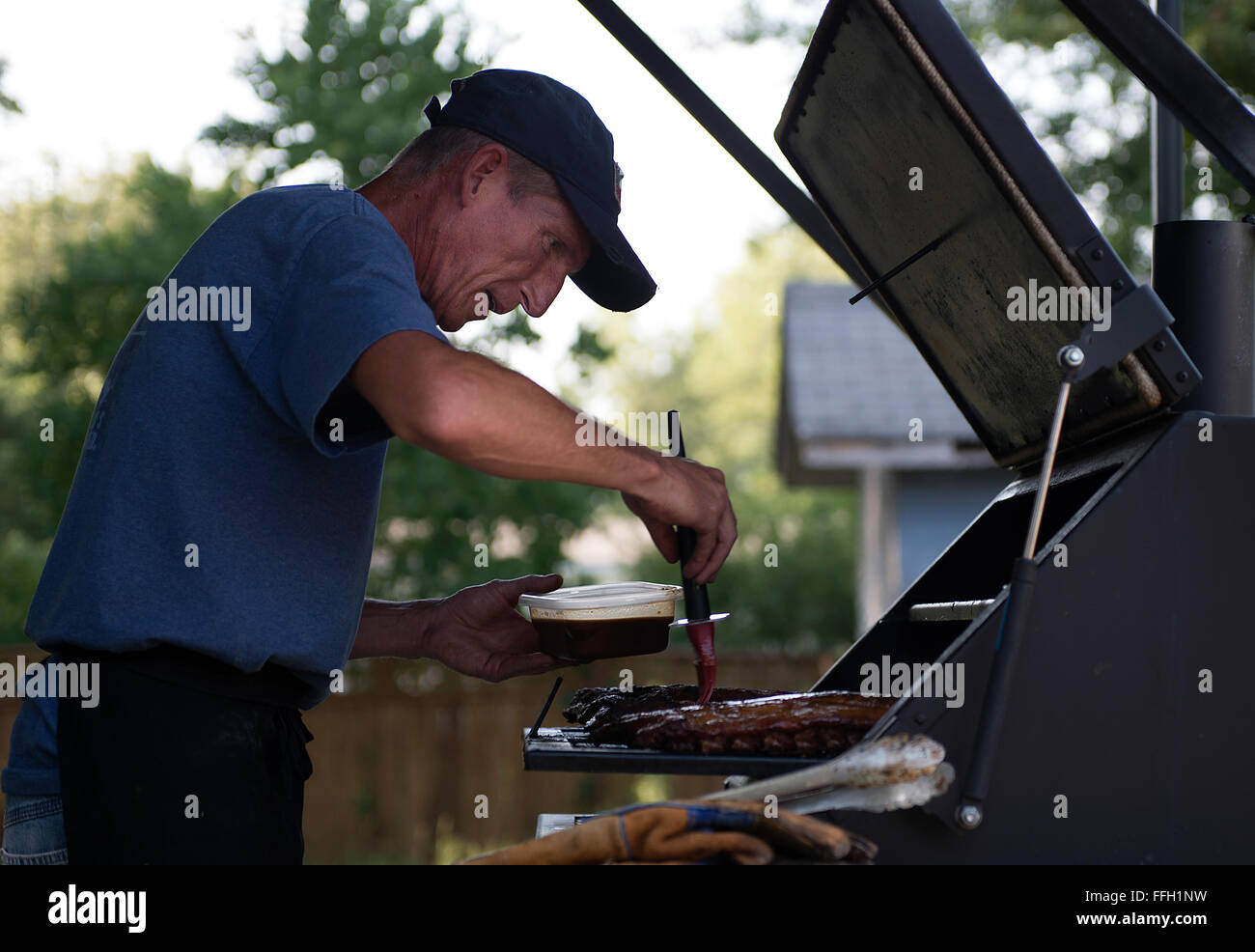 Tech. Sgt. Todd Houghton tries out a new barbecue sauce on ribs in his backyard. At the time, Houghton was honing - Stock Image