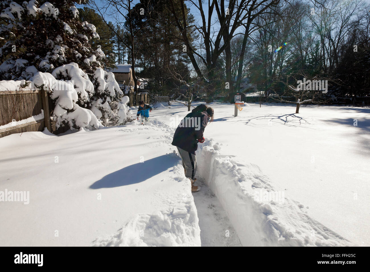 Woman shoveling deep snow from driveway - Virginia USA - Stock Image