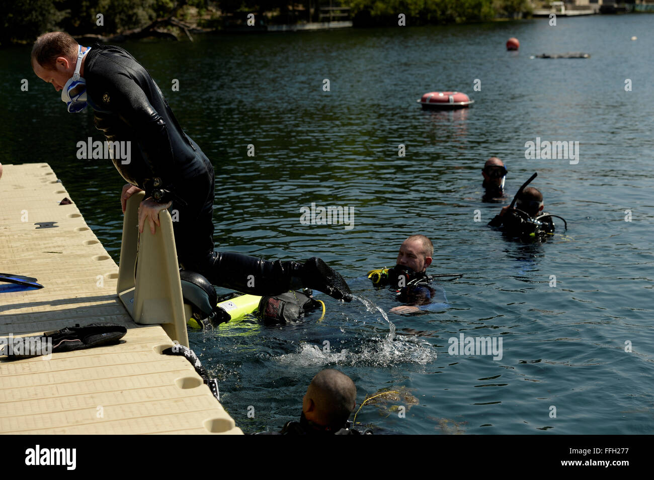 Keith Morlan climbs onto the dock while participating in a scuba diving class at Spring Lake in San Marcos, Texas. - Stock Image