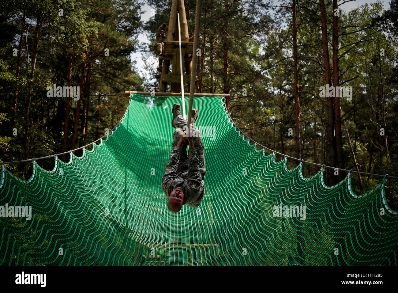 Staff Sgt. Stephen Moore climbs across the inverted rope challenge on an obstacle course at Grafenwoehr Training - Stock Image