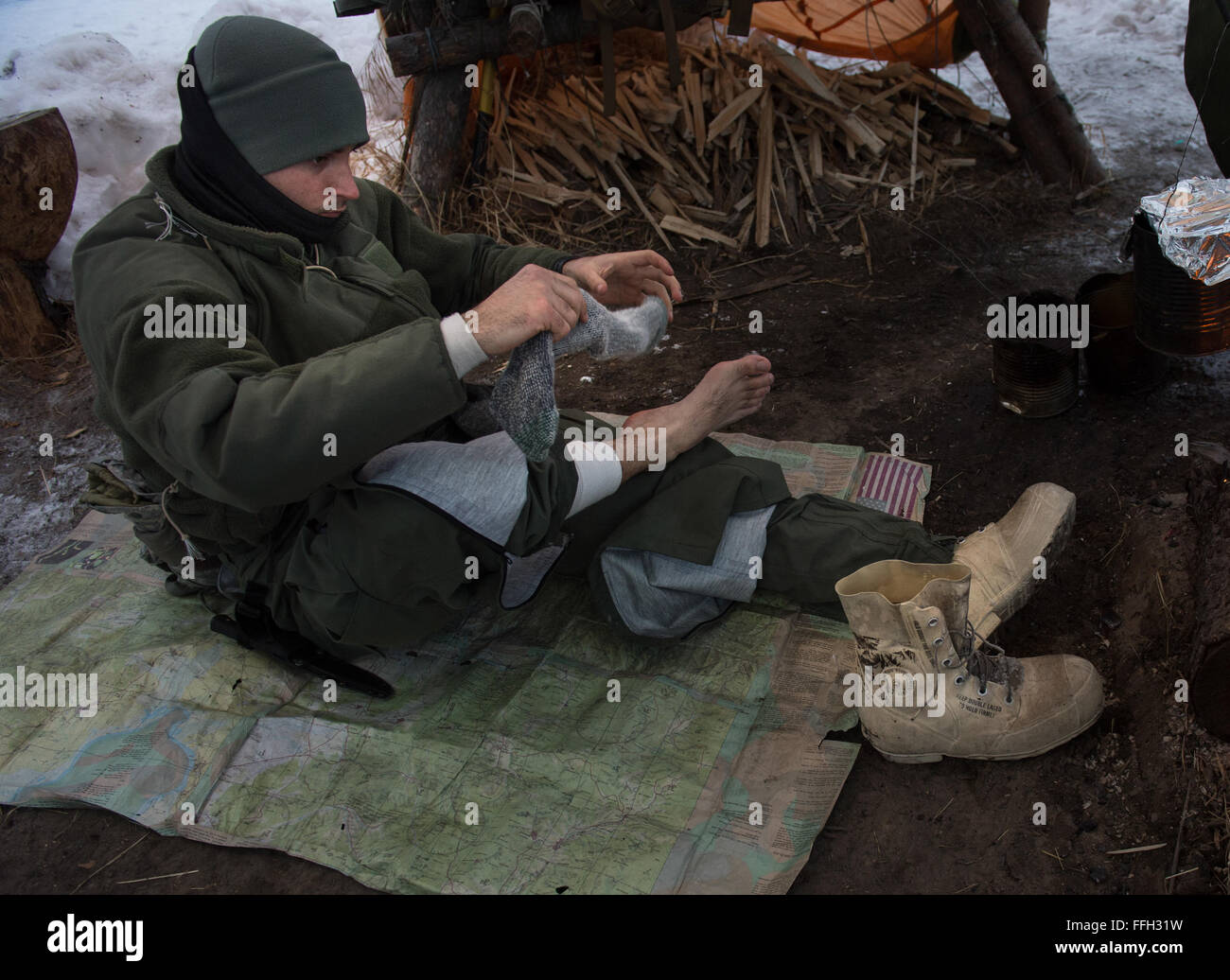 U.S. Air Force 1st Lt. Evan Wells, 37th Helicopter Squadron, UH-1N Huey pilot, changes socks during arctic survival - Stock Image