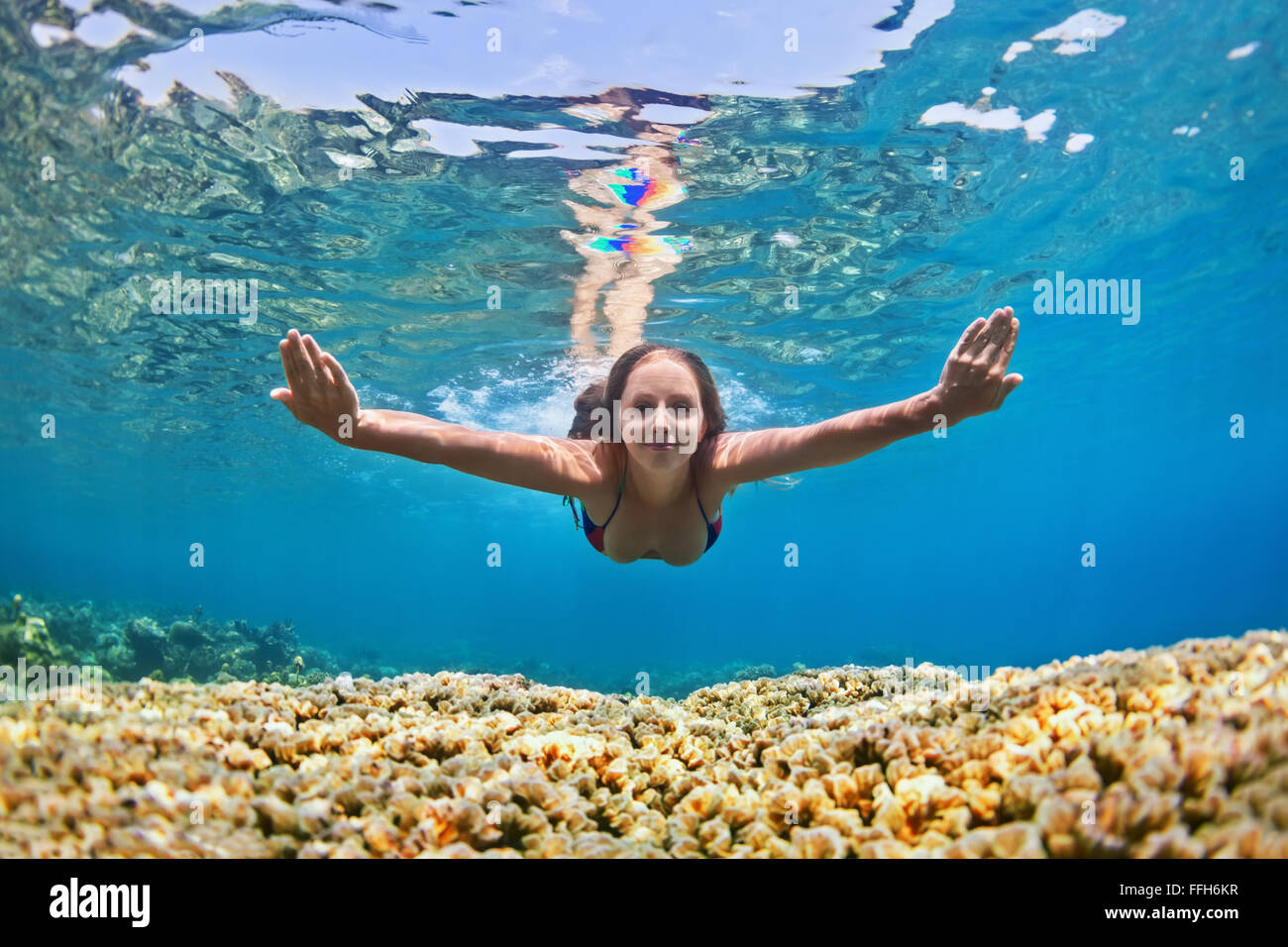 Happy beautiful girl - young woman dive underwater with fun over coral reef in sea pool. - Stock Image