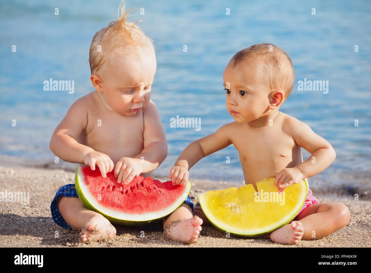 After sea swimming asian baby girl and white boy have a fun and eat fresh fruits on sand beach. - Stock Image