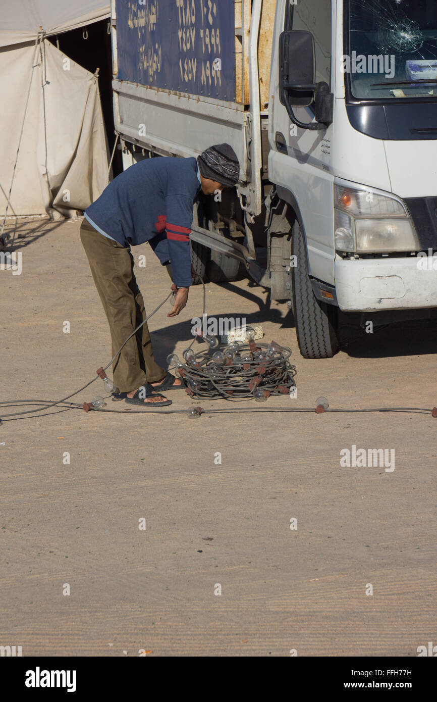Worker coils a set of lights - Stock Image