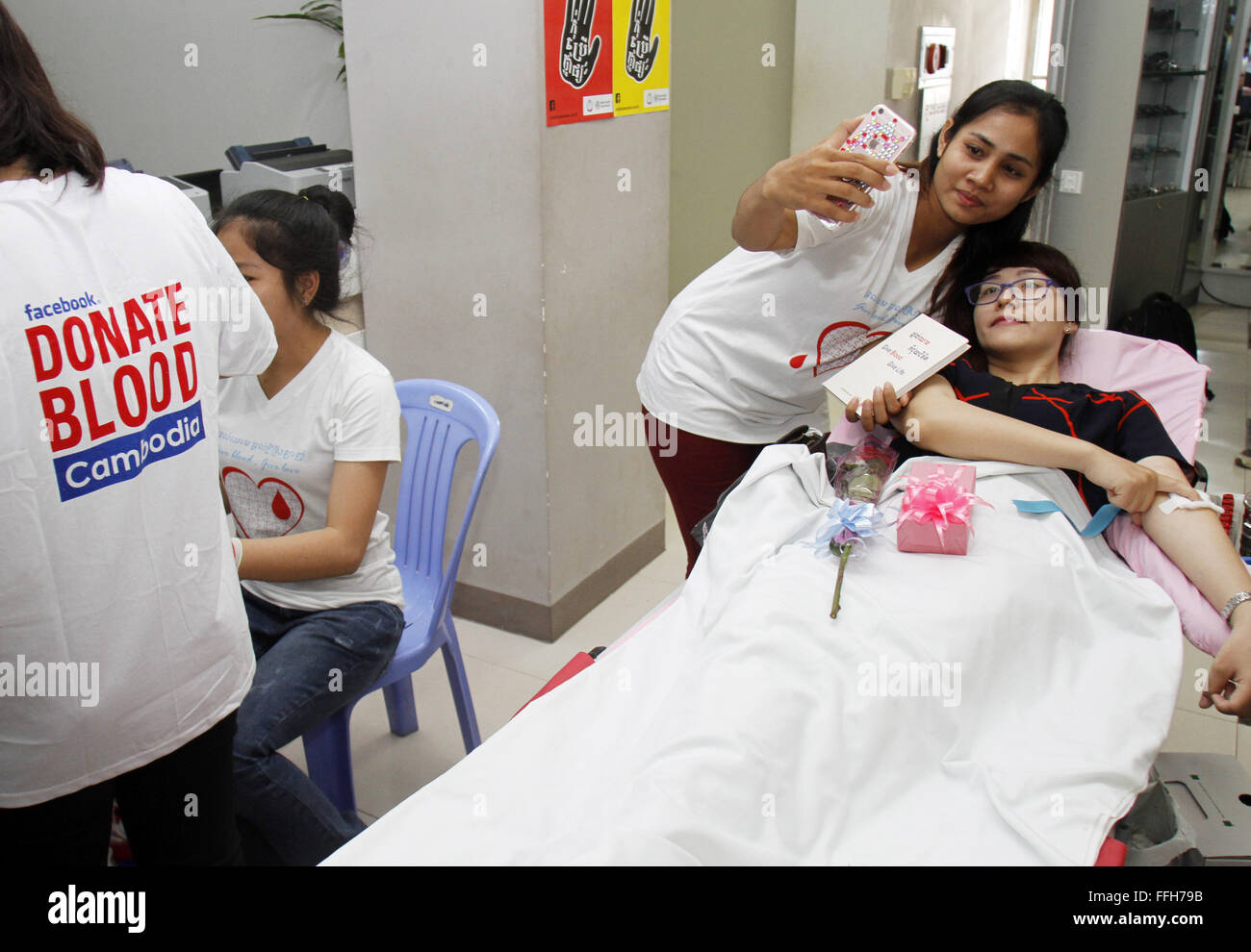 Phnom Penh, Cambodia. 14th Feb, 2016. A young woman takes a selfie with her friend who donates blood in Phnom Penh, - Stock Image