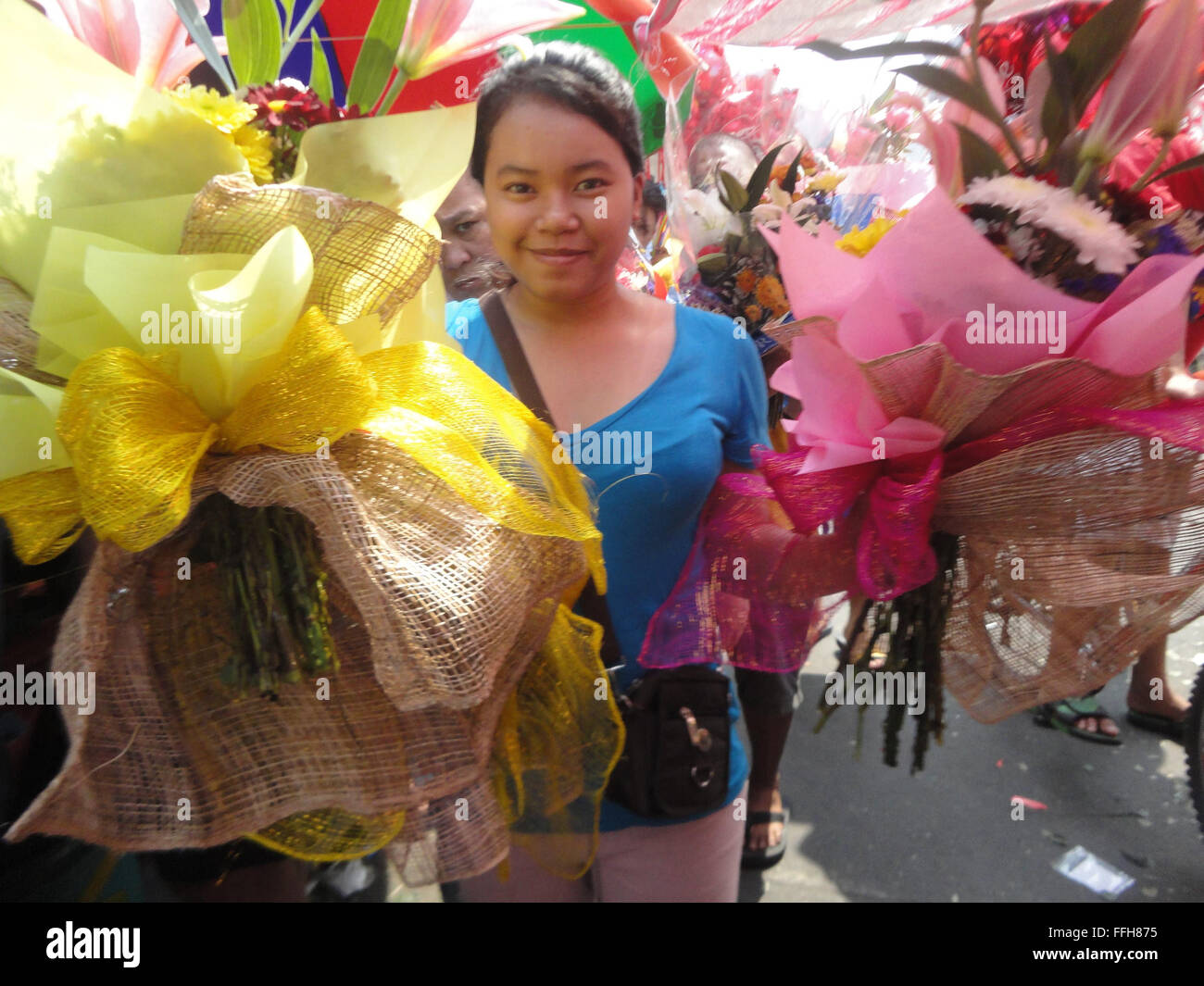 Manila, Philippines. 14th Feb, 2016. Filipinos carry bouquets of roses along the Dangwa flower market in Manila, Stock Photo