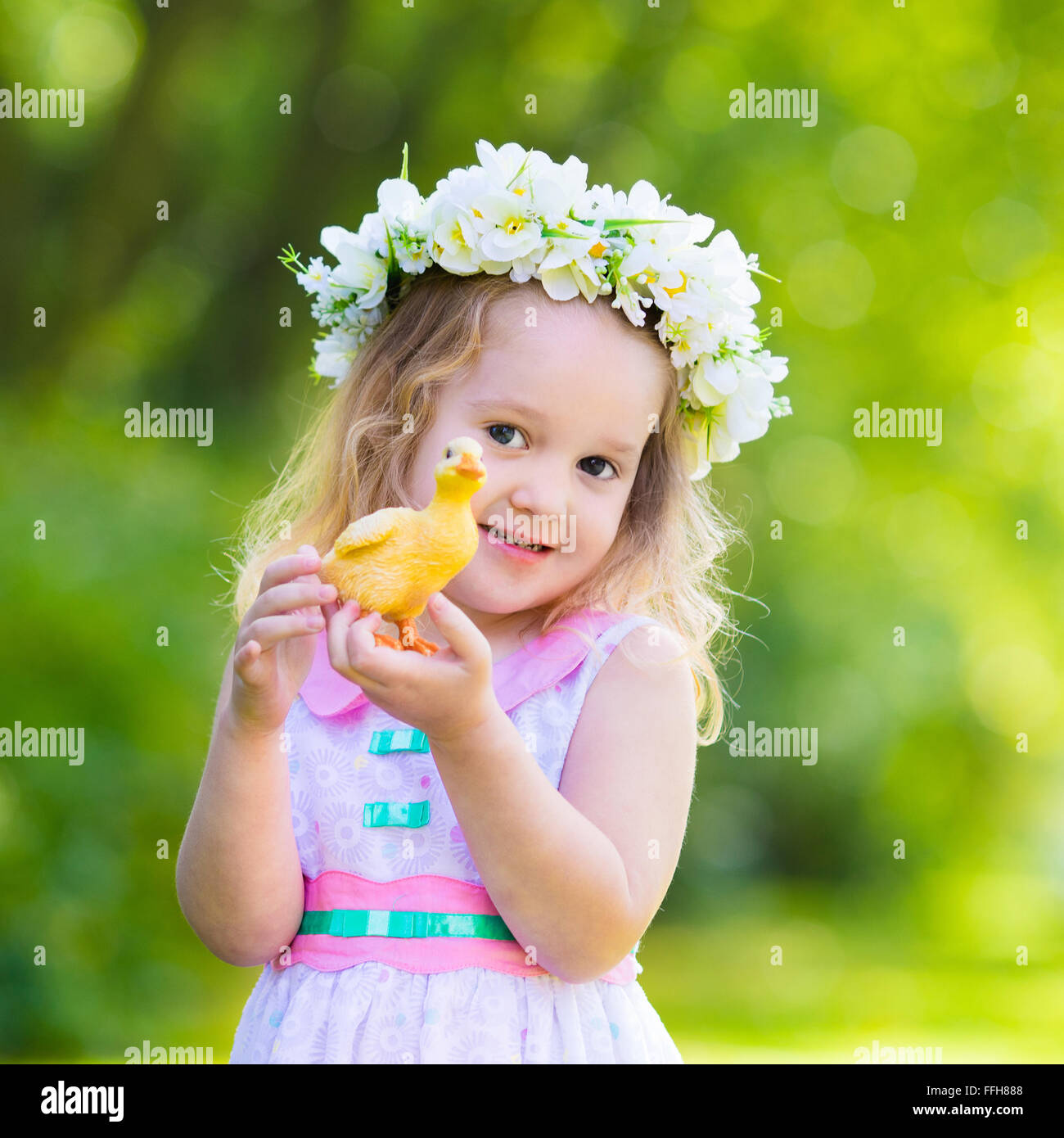 Little girl having fun on easter egg hunt kid in flower crown stock little girl having fun on easter egg hunt kid in flower crown playing with toy duck or chicken children searching for eggs izmirmasajfo Gallery