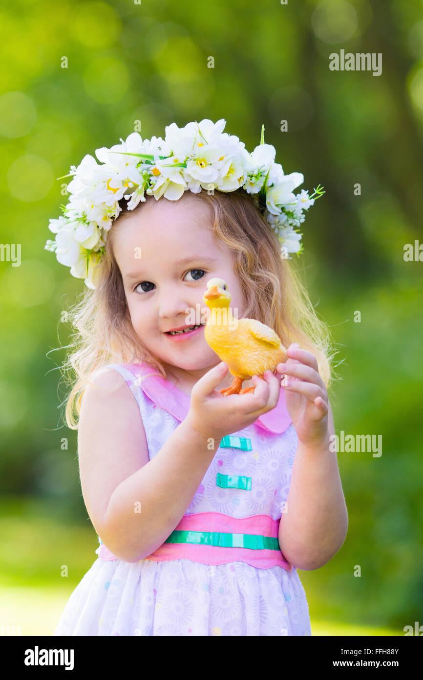 Little girl having fun on easter egg hunt kid in flower crown stock little girl having fun on easter egg hunt kid in flower crown playing with toy duck or chicken children searching for eggs izmirmasajfo