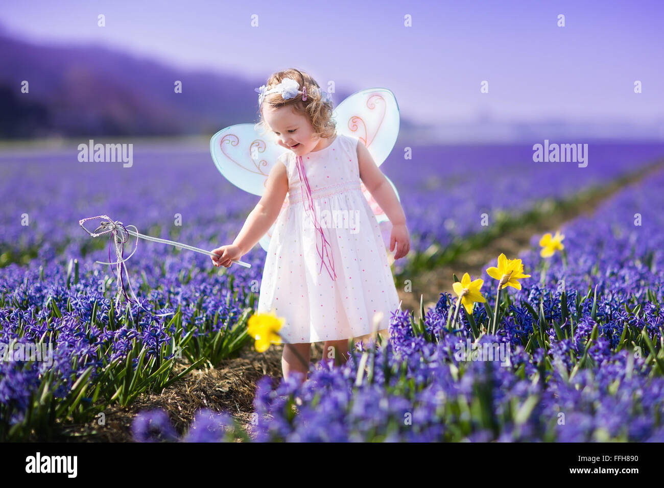 fbd3b6c4dff9 Cute curly little girl in flower crown and fairy costume with wings ...