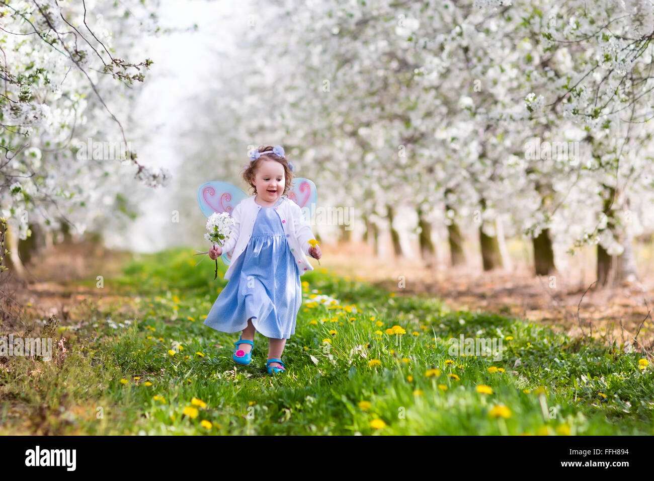 Little girl in fairy costume with wings flower crown and magic wand little girl in fairy costume with wings flower crown and magic wand playing in blooming apple tree garden on easter egg hunt izmirmasajfo Gallery