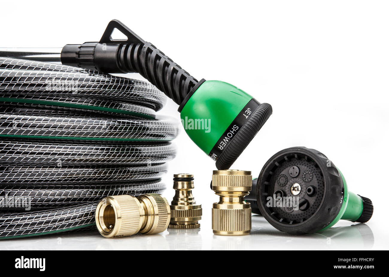 A  garden hose with a sprayer and fittings on a white background - Stock Image