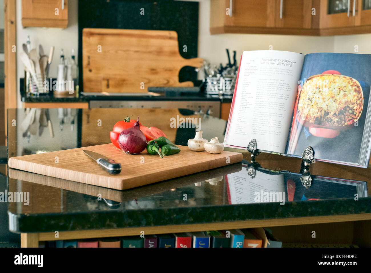 Preparation of food in a domestic kitchen using a chopping board, knife and recipe book - Stock Image