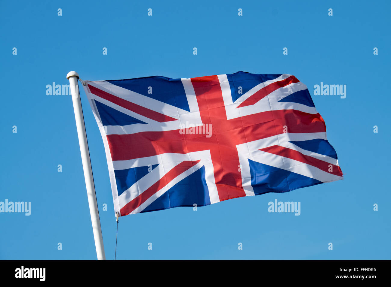 The union flag fluttering atop a white flagpole on a sunny day against a clear blue sky - Stock Image