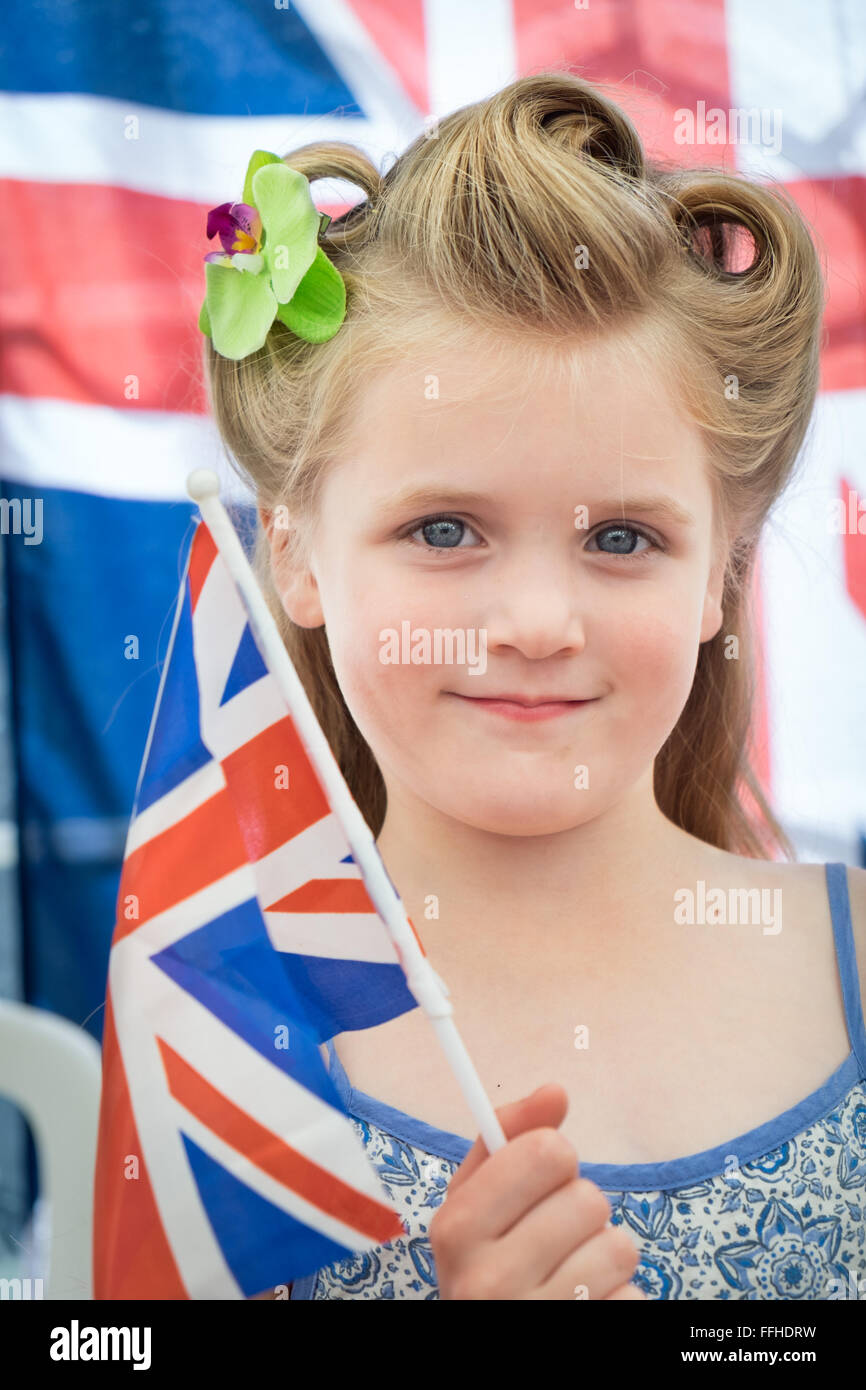 A young blonde girl with her hair in a 1940's style showing patriotism, holding a union flag at a vintage event - Stock Image