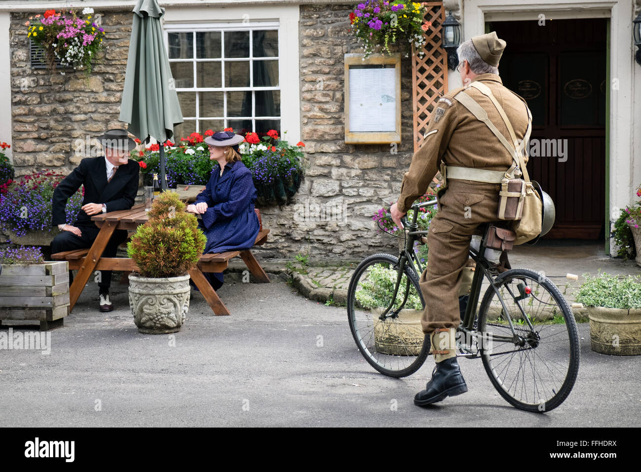 Participants in a Britain at war re-enactment day in WW2 period 1940's dress, outside a pub in the United Kingdom - Stock Image