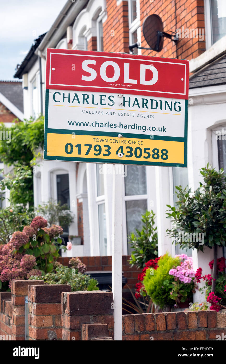 The marketing for sale sign boards of local estate agent Charles Harding outside homes on a street in Swindon Wiltshire - Stock Image