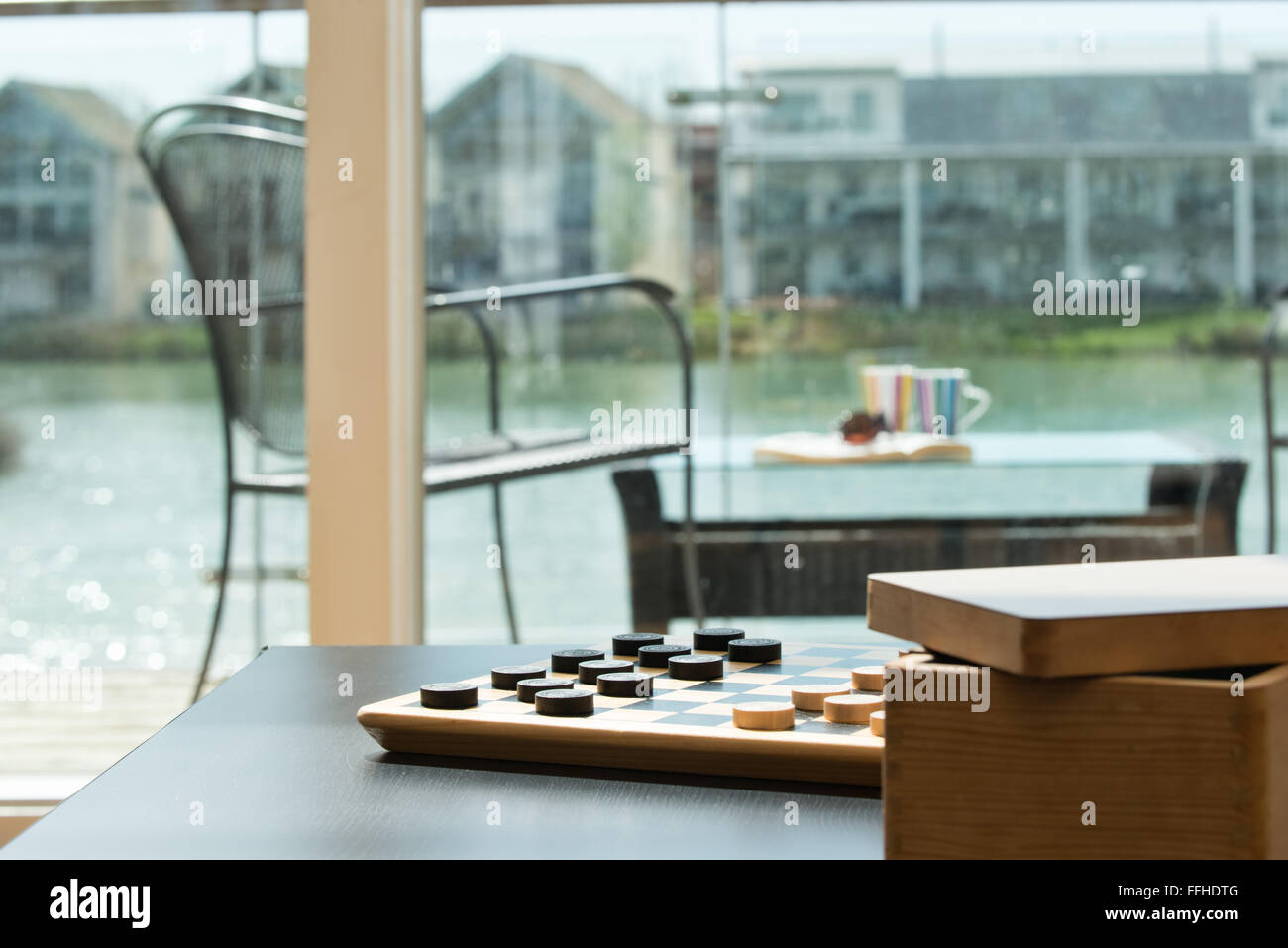 A checkers board, set, awaiting opponents to start a game in a holiday home overlooking water Stock Photo