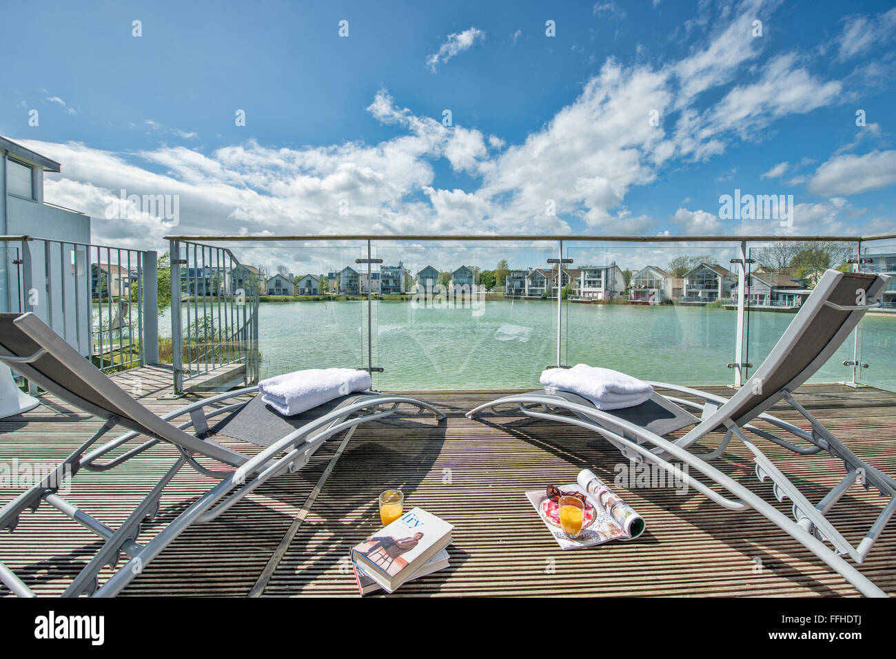 2 deck chairs on decking at a holiday residence in the Cotswolds, UK with a waterside view awaiting occupants - Stock Image