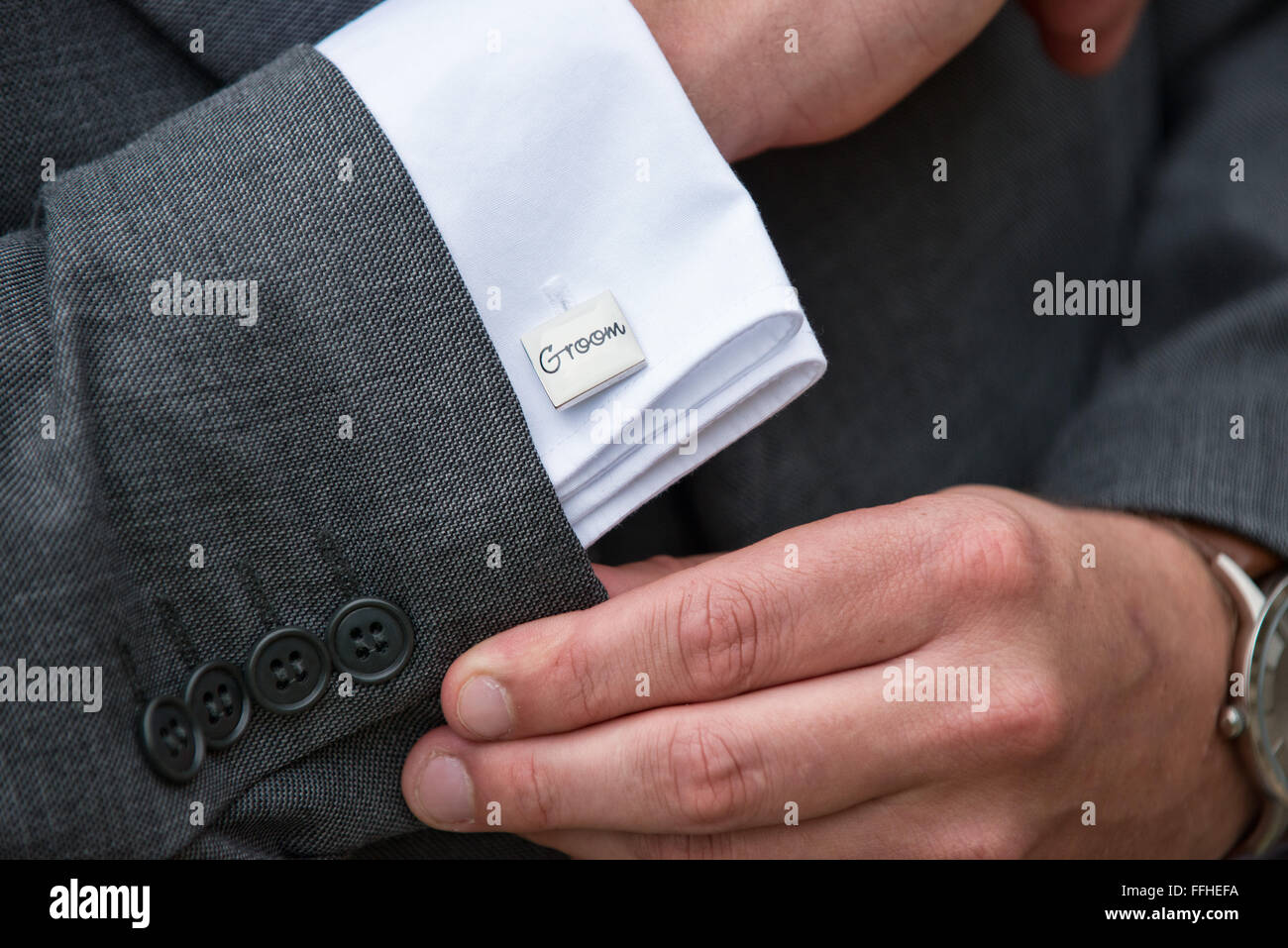 A grooms hands adjusting his sleeves at his wedding, revealing his shirts cuff & silver cufflinks displaying - Stock Image