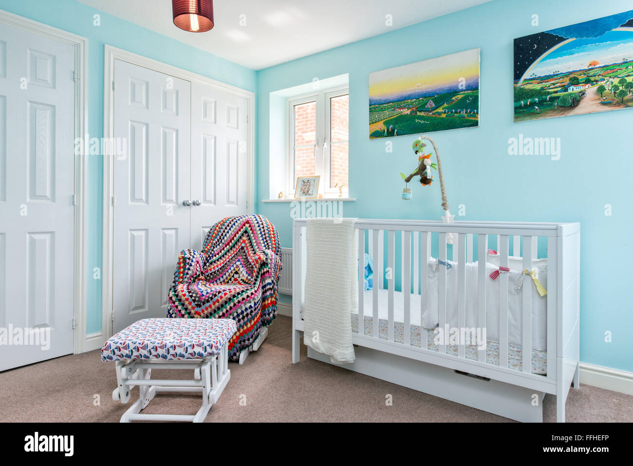The nursery of a young child decorated in blue & white with a cot and nursing chair covered with a throw - Stock Image
