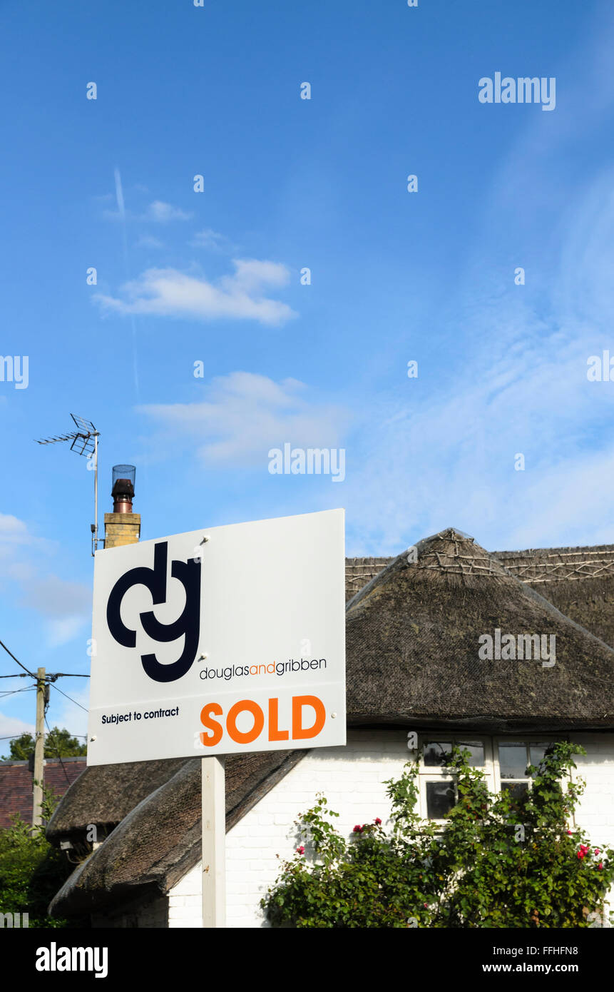 An estate agents sign outside a thatched cottage in Uffington, Oxfordshire, England, UK. Stock Photo