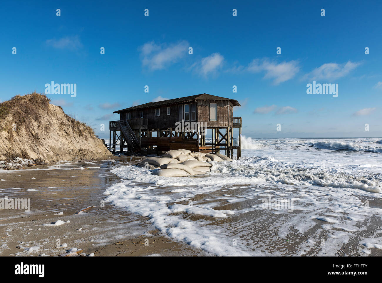 Beach house on stilts surrounded by high tide surf Nags Head Outer