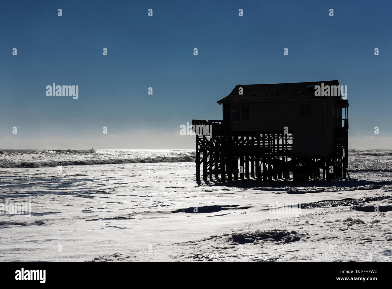Beach house on stilts surrounded by high tide surf, Nags Head, Outer Banks, North Carolina, USA - Stock Image
