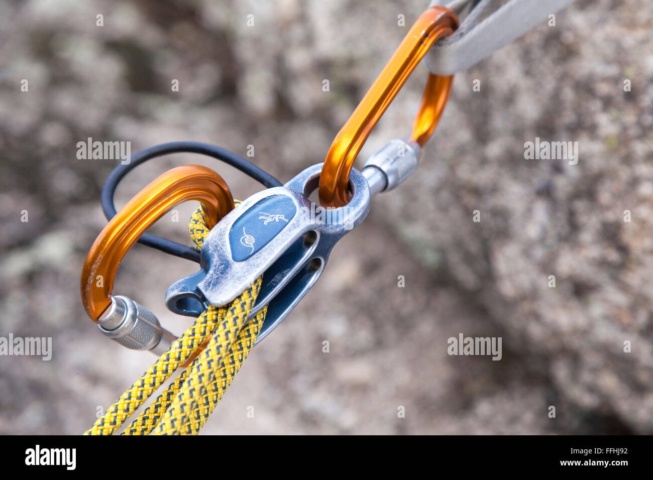 Belay device close up. A belay device is a mechanical piece of climbing equipment used to control a rope during - Stock Image