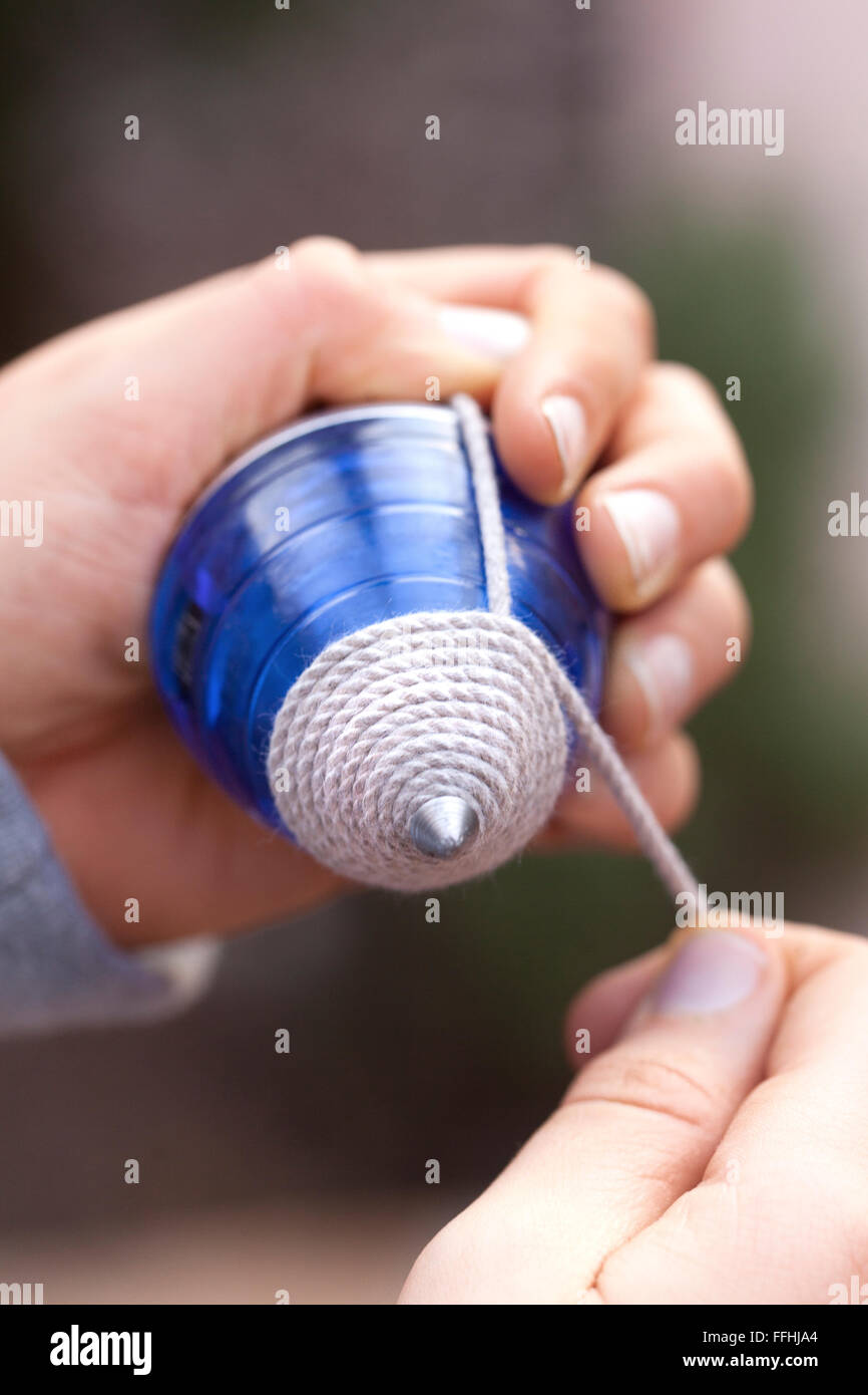 A boy rolling the string in a plastic spinning top. A modern version of an old traditional toy. - Stock Image
