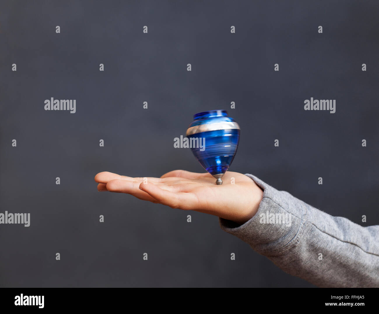 A boy spinining a top on his hand. Dark background and copy space for your text. - Stock Image