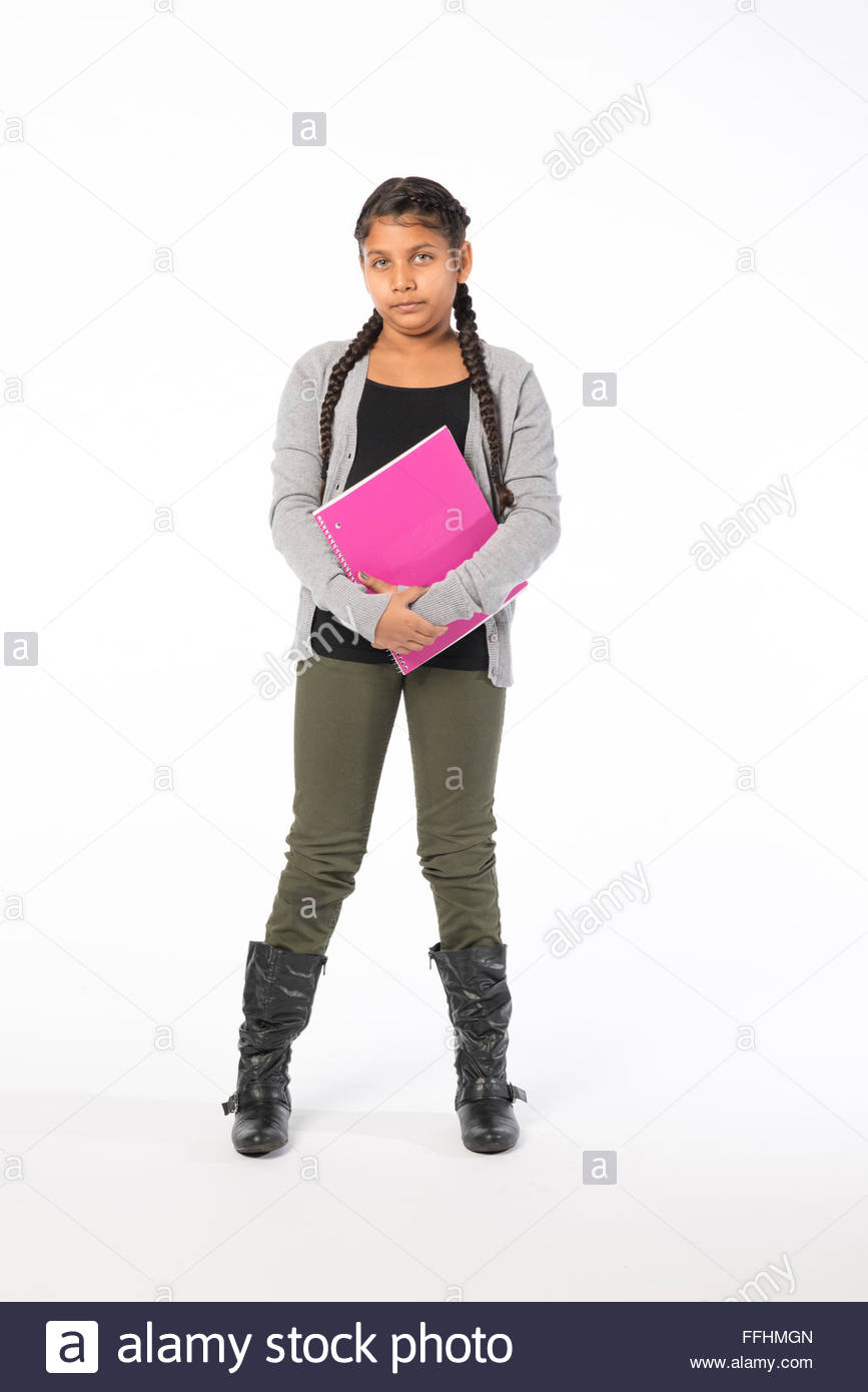 Young Indian or South Asian tween girl student standing on a white background holding a pink note book. - Stock Image