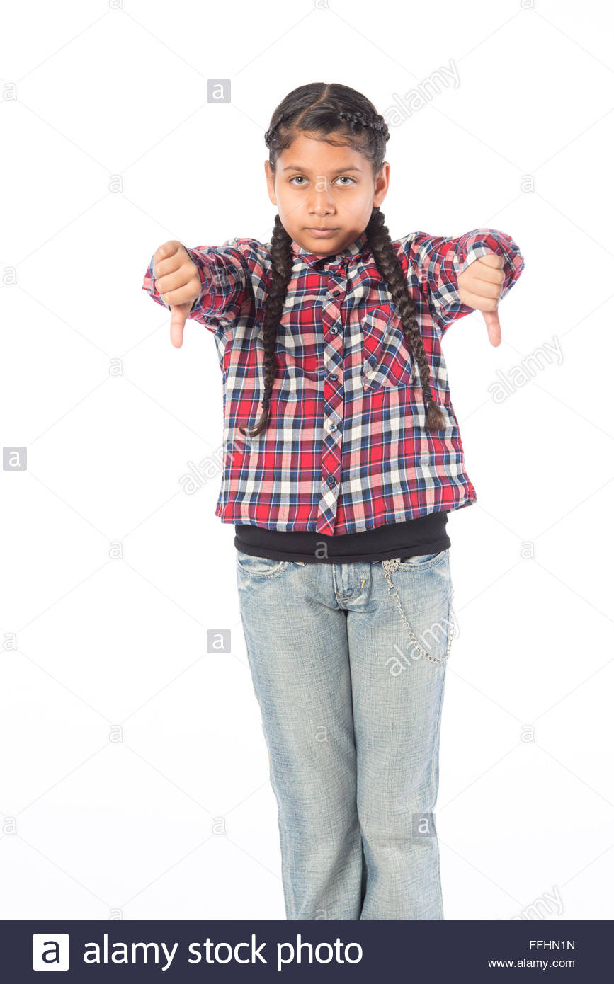 young Asian Indian girl standing on a white background in casual school cloths giving thumbs down sign - Stock Image