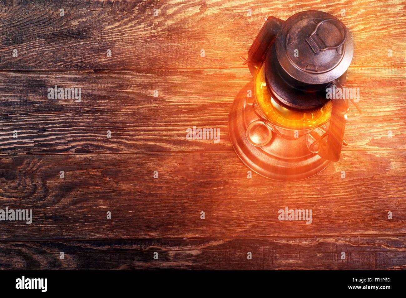 Old rusty kerosene lantern on wooden structured floor - Stock Image
