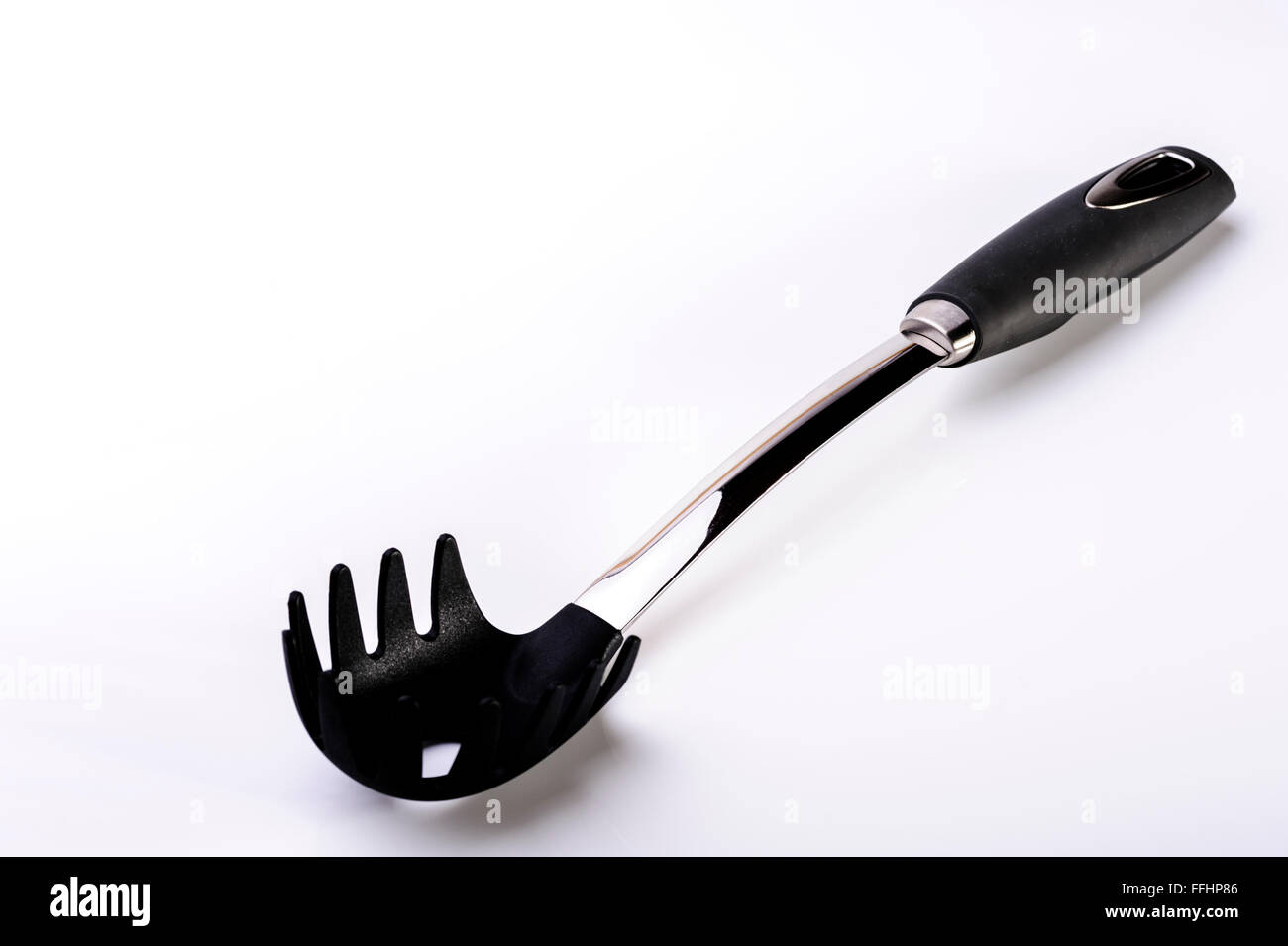 Spaghetti or pasta scoop.Kitchen equipment untensil. - Stock Image