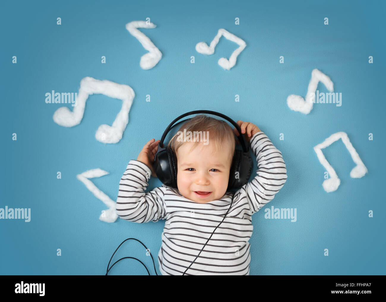 little boy on blue blanket background with headphones - Stock Image