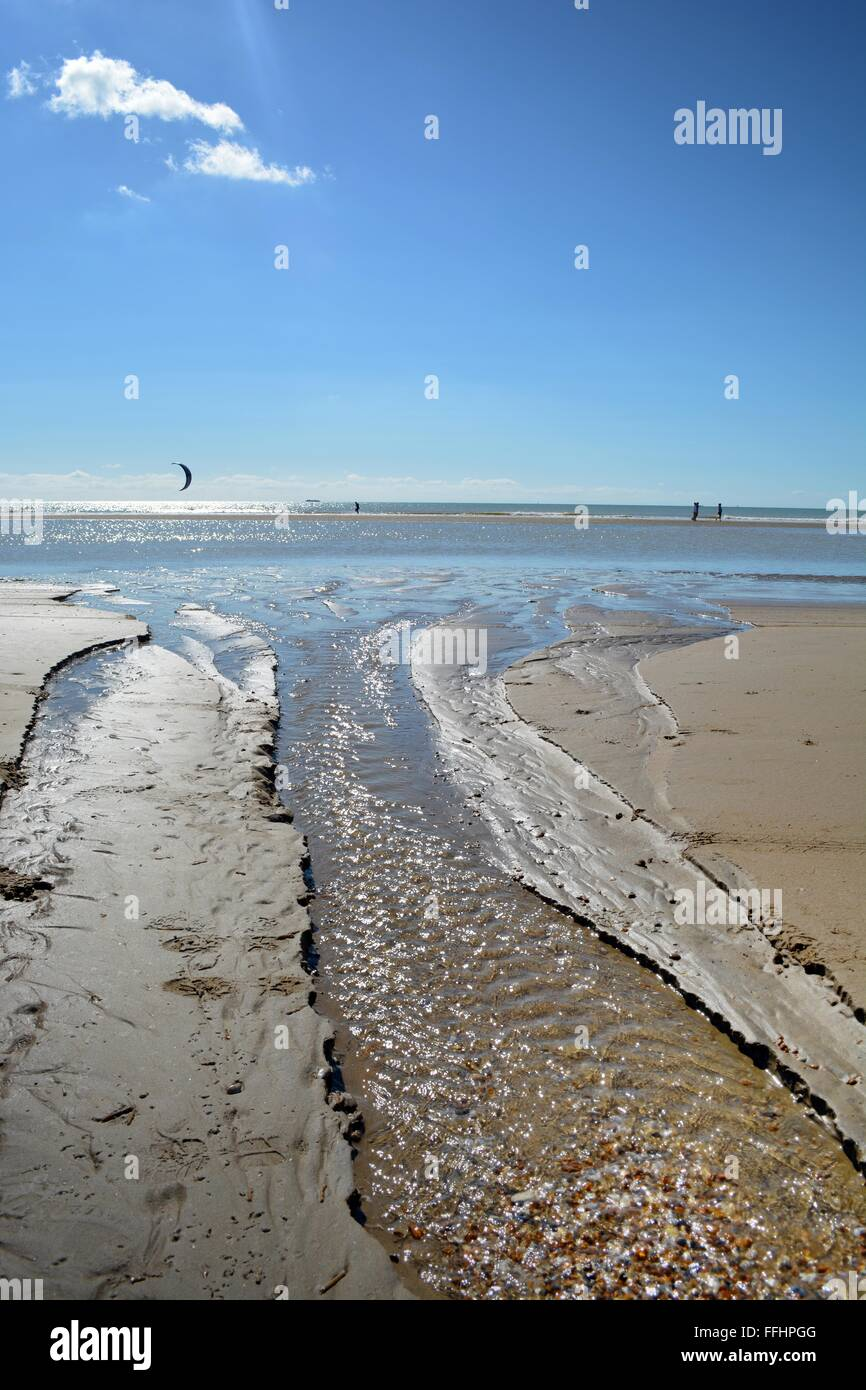 freshwater stream running into a sparkling sea at Camber Sands in Sussex, England, with kite surfers out at sea - Stock Image